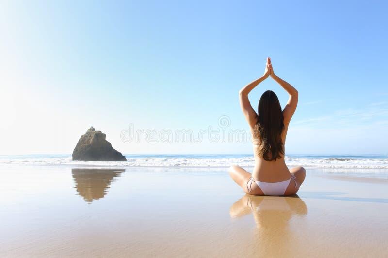 行使在海滩的妇女瑜伽 库存图片