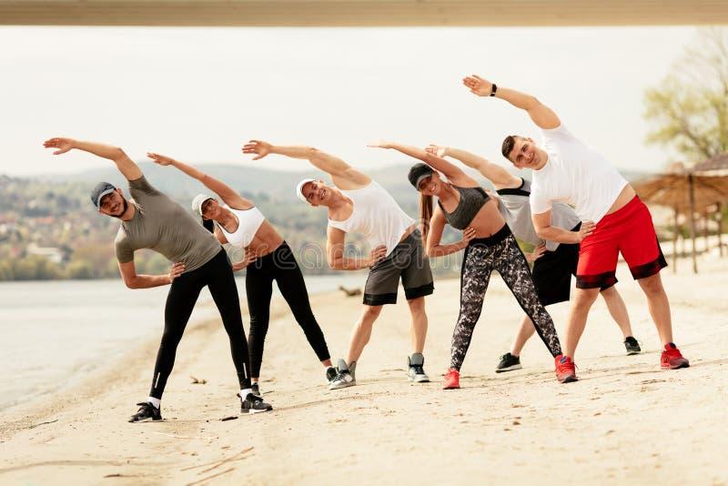 行使在海滩的小组朋友 免版税图库摄影