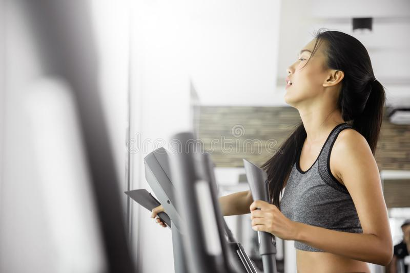 行使在省略教练员机器的亚裔妇女 库存图片