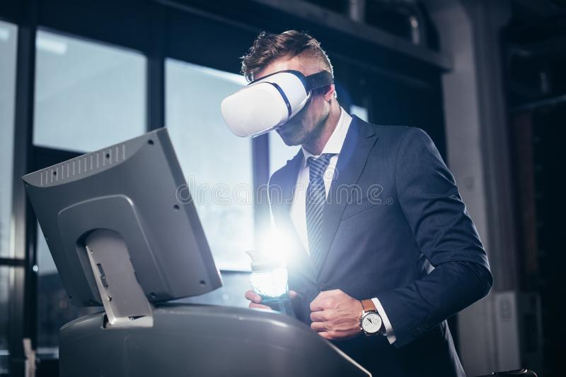 行使在踏车的商人和虚拟现实耳机低角度视图在衣服的 免版税图库摄影