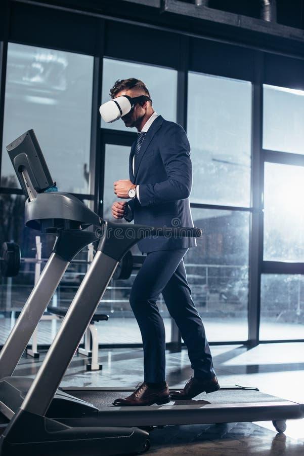 行使在踏车的商人和虚拟现实耳机侧视图在衣服的 免版税库存图片