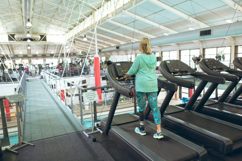 行使在踏车的残疾活跃资深妇女在健身演播室 库存照片