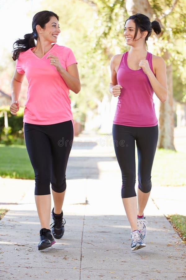 行使在郊区街道上的两个女性赛跑者 库存照片