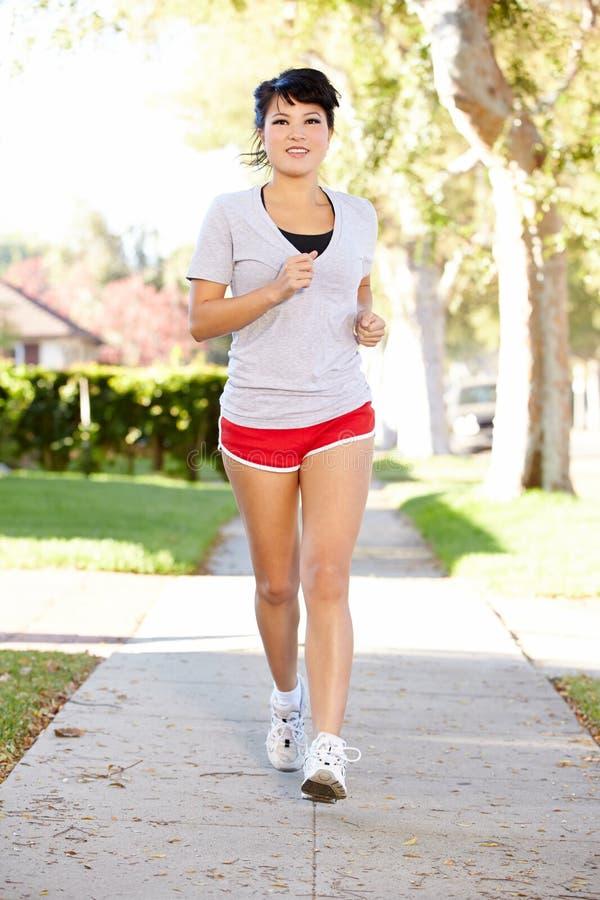行使在郊区街道上的女性赛跑者 免版税库存图片