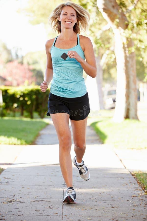 行使在郊区街道上的女性赛跑者 免版税库存照片