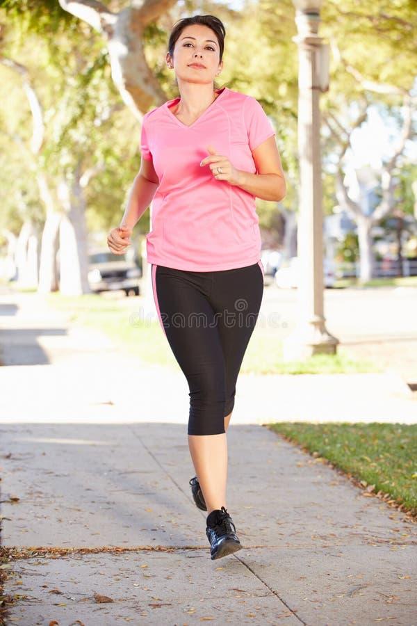 行使在郊区街道上的女性赛跑者 免版税图库摄影