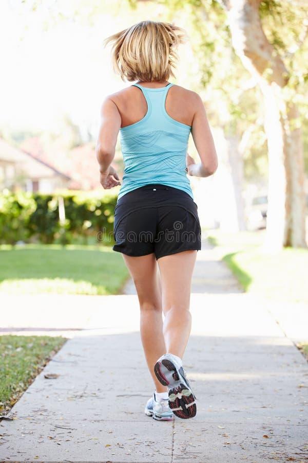 行使在郊区街道上的母赛跑者背面图 免版税库存图片