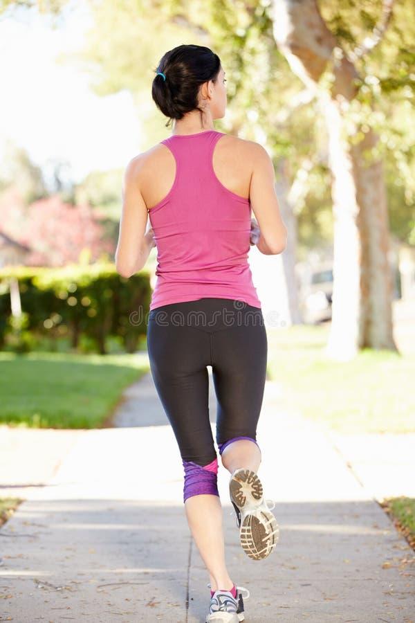 行使在郊区街道上的母赛跑者背面图 库存图片