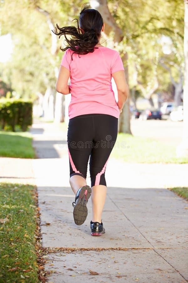 行使在郊区街道上的母赛跑者背面图 库存照片