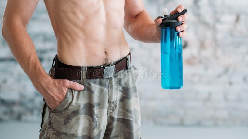 行使水瓶适合男性躯干的水合作用 库存照片