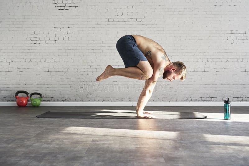 行使瑜伽asana的肌肉被刺字的运动员在晴朗的体育俱乐部增加里面 适合的赤裸上身的男性健身模型 库存图片