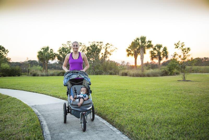 行使的妇女跑步和户外,当推挤她的婴儿推车的时婴孩 免版税库存图片
