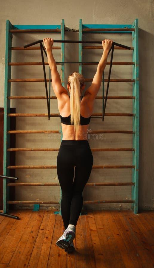 行使运动的运动员的妇女做在健身房的引体向上从后面 库存图片