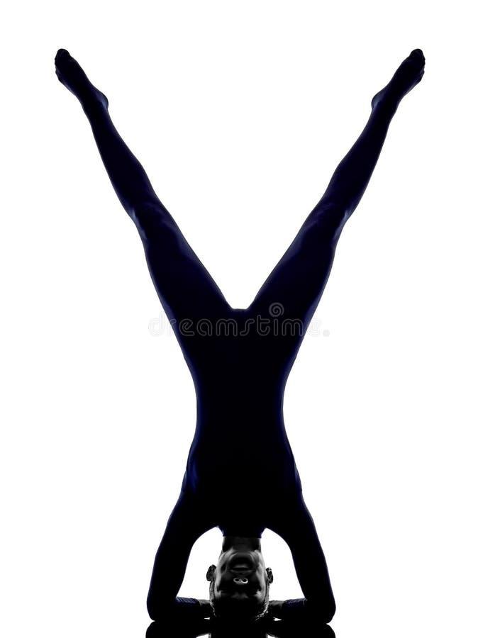 行使vrschikasana蝎子姿势瑜伽剪影的妇女 免版税库存照片