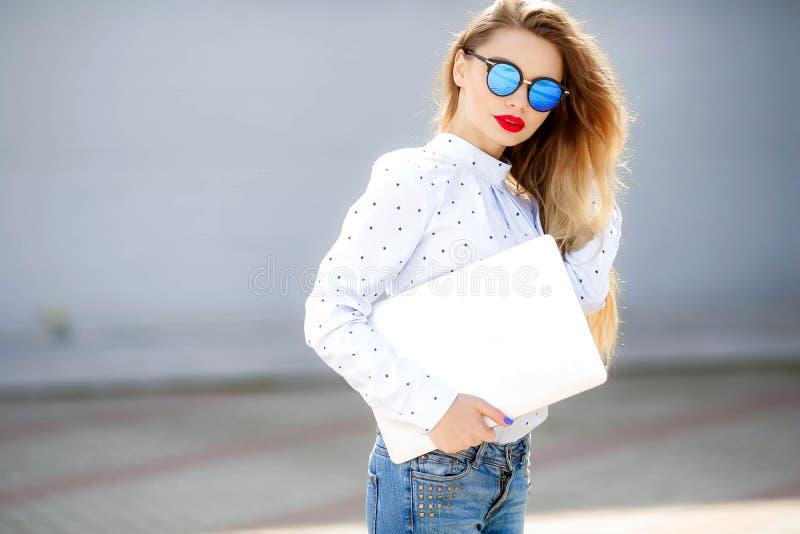 行动可爱的妇女时尚画象牛仔裤的有长发的 牛仔裤衣服的女孩 有新的牛仔布的迷人的夫人 免版税库存照片