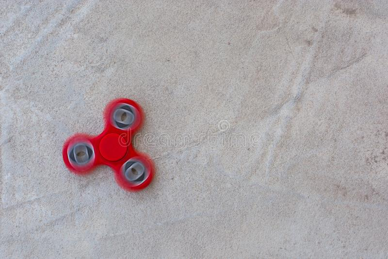 行动应力消除玩具的红色坐立不安锭床工人在具体背景 免版税库存图片