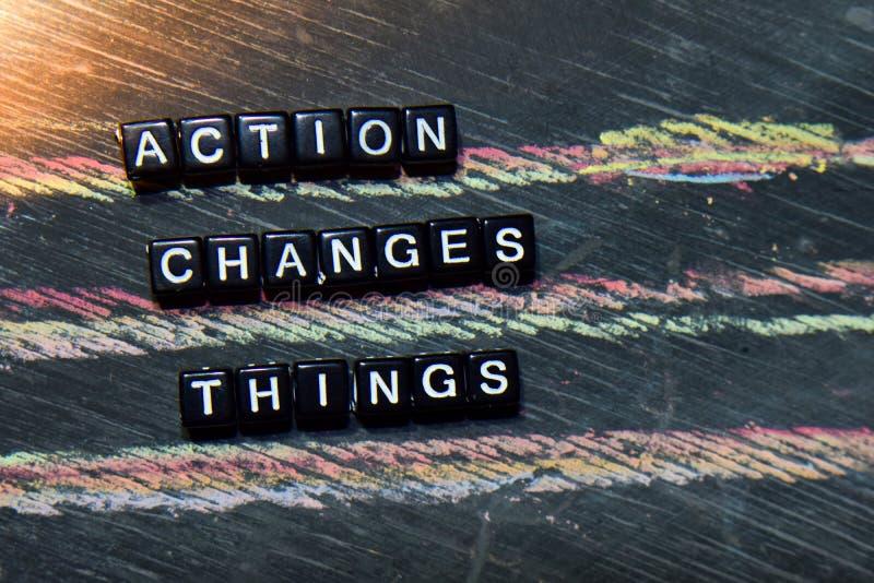 行动改变事-在木块的行动 发怒被处理的图象有黑板背景 库存图片