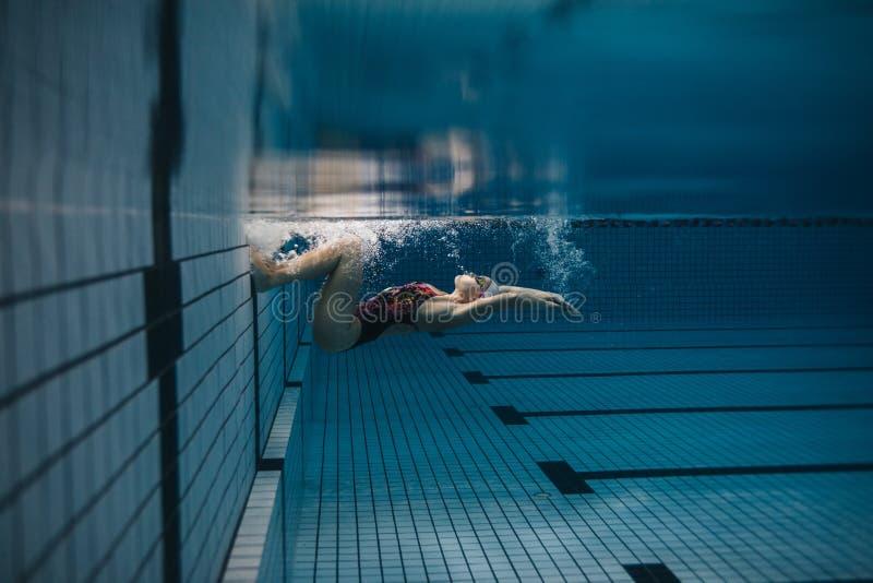 行动的女性游泳者在游泳池里面 免版税图库摄影