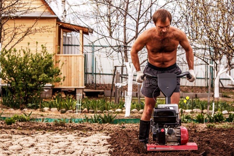 行动的汽油耕地机对种田的剧情 免版税库存图片