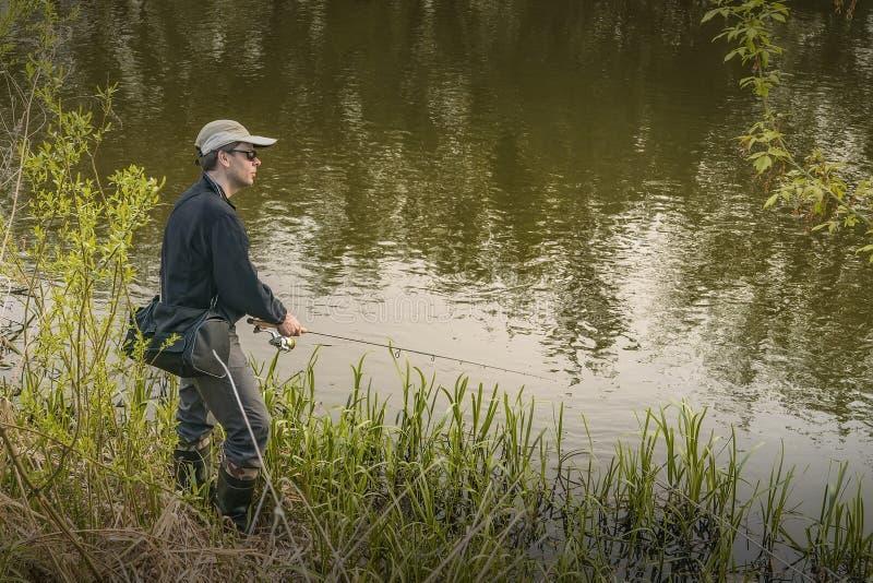 ?? 行动的渔夫,人由实心挑料铁杆的抓住鱼 图库摄影