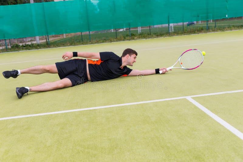 行动的英俊的男性网球员在下落的比赛期间  免版税图库摄影