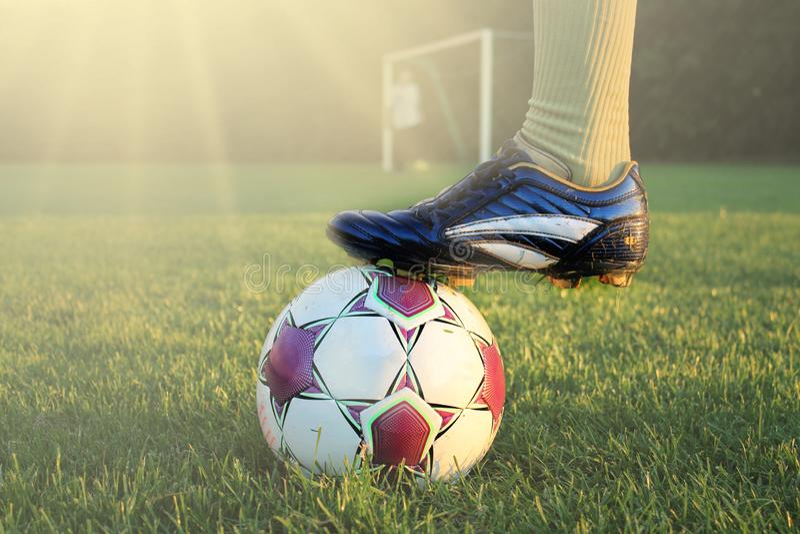 行动的足球运动员与橄榄球在明亮地被点燃的室外体育场内 在前景的焦点和与浅深度的足球  库存图片