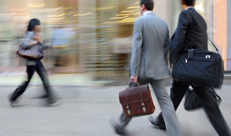 行动走在街道上的被弄脏的商人 图库摄影