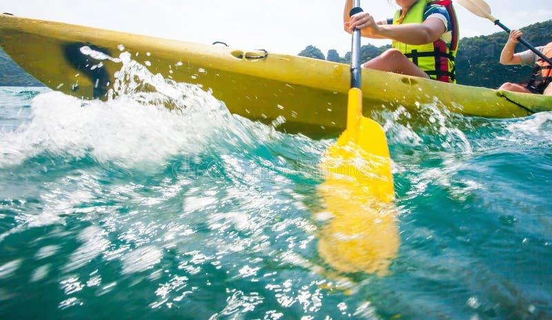 行动迷离,探险家妇女关闭救生衣的艰苦用浆划皮船与的在晴朗,冒险飞溅在热带海 库存照片