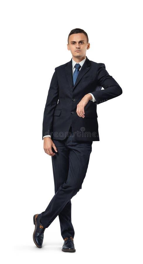 行动年轻的商人站立与盘的腿和,如他在他的胳膊倾斜 免版税库存图片