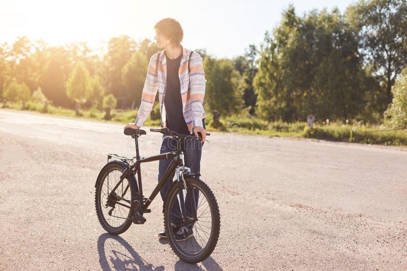 行家人佩带的衬衣和牛仔裤,站立与他的自行车,看在旁边,当等待他的朋友来时 少年去 免版税库存照片