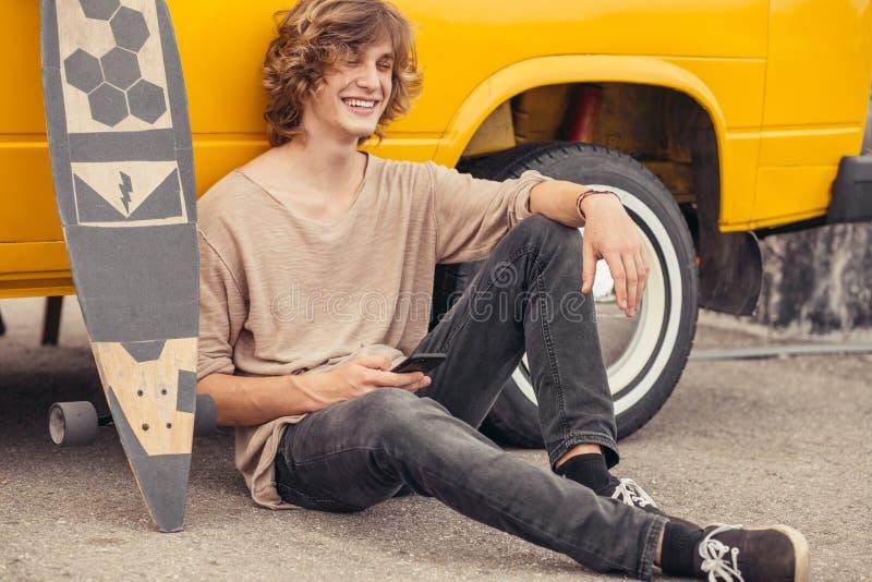 行家人坐longboard使用他的电话 图库摄影