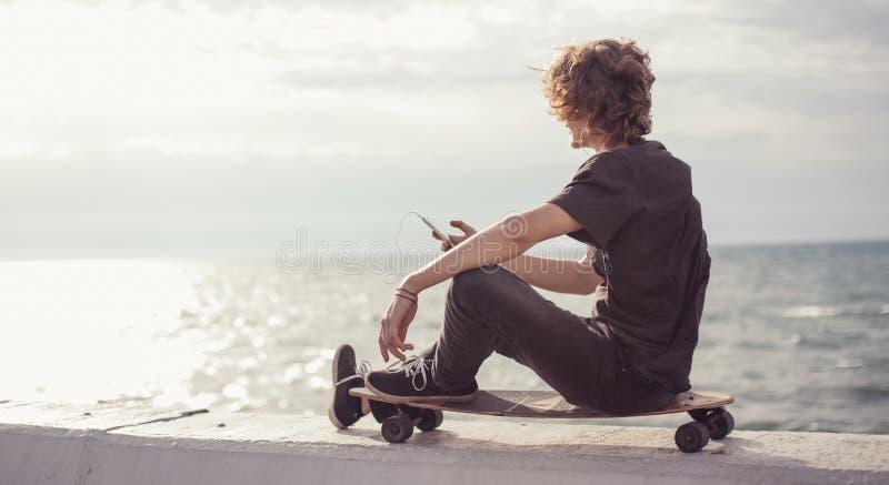 行家人坐longboard使用他的电话 免版税库存图片