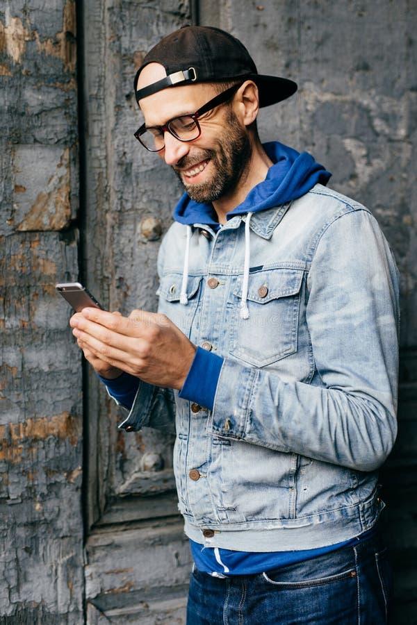 行家人垂直的画象牛仔布衬衣、盖帽和eyewear的在他的手上的拿着现代电话有高兴的表示whil 免版税库存图片