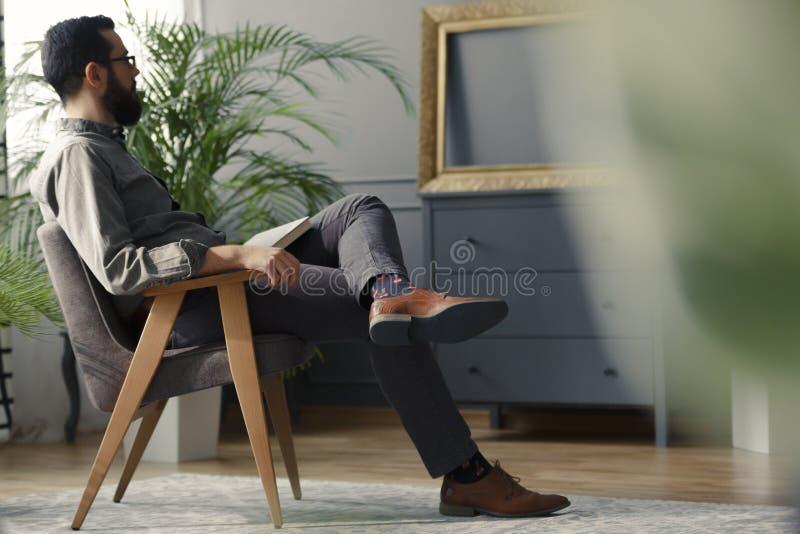行家低角度坐在灰色葡萄酒的木扶手椅子 免版税图库摄影