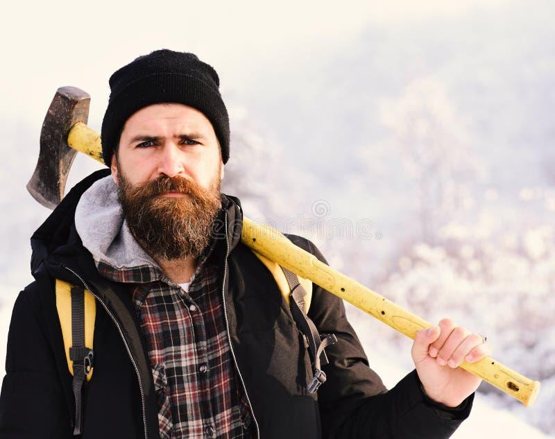 行家住在森林并熟悉森林的人概念 冬天衣裳的强壮男子有背包的 免版税库存照片