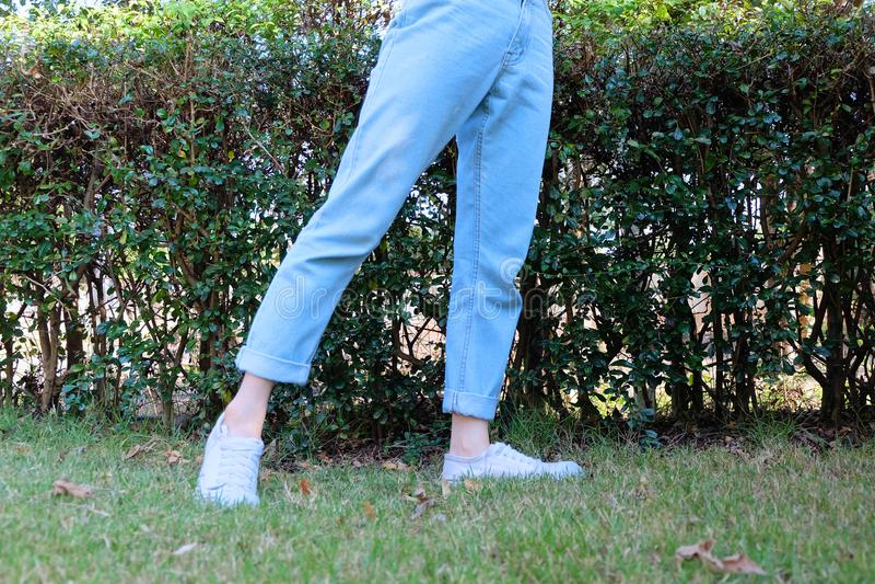 行家偶然白色运动鞋 女性站立的佩带的白色鞋子和蓝色牛仔裤裤子在绿草自然背景 库存图片