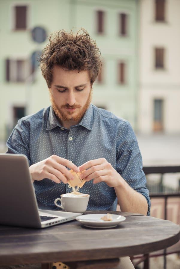 年轻行家喝咖啡在酒吧 免版税图库摄影