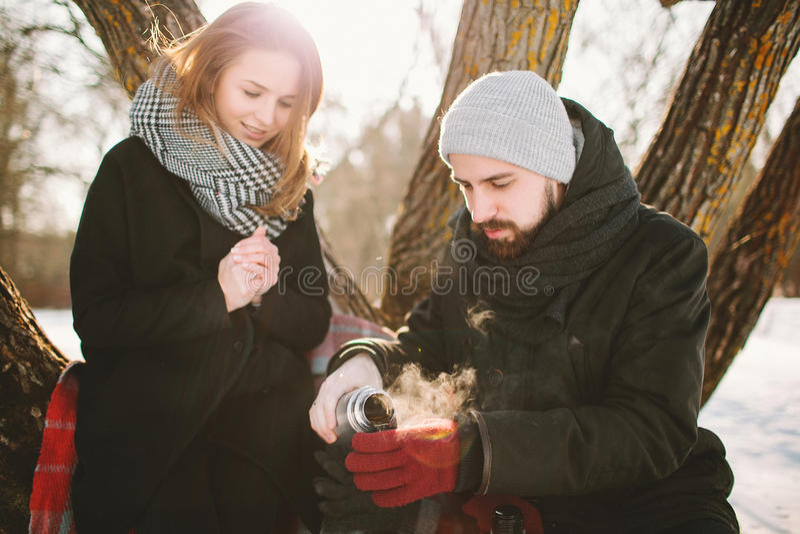 行家夫妇在冬天停放用从热水瓶的热的茶 图库摄影