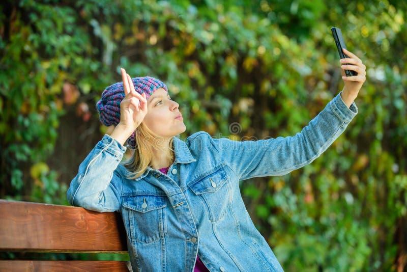行家女孩在公园做selfie Selfie时间 放松在长凳 行家春天时尚 视讯会议 喂我在这里 库存图片