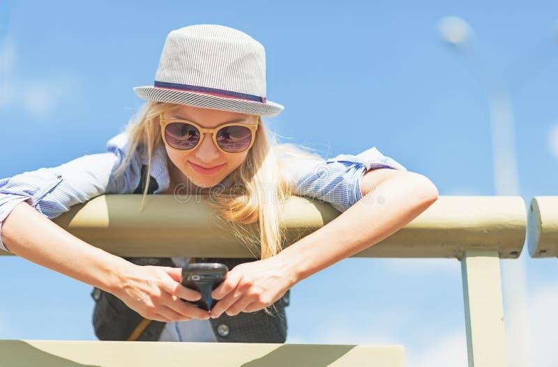 行家女孩在城市街道上的文字sms 免版税库存照片