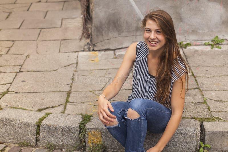 年轻行家女孩坐在街道上的遏制在老镇 库存照片