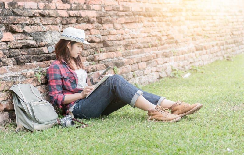 行家女孩坐草并且使用智能手机发现地方 库存图片