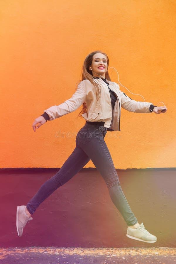 年轻行家女孩跳跃反对桔子和听到音乐由耳机由智能手机 都市的样式 强光和 库存照片