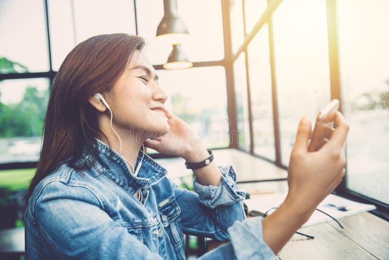 行家妇女享受从电话app的听的音乐 免版税库存照片