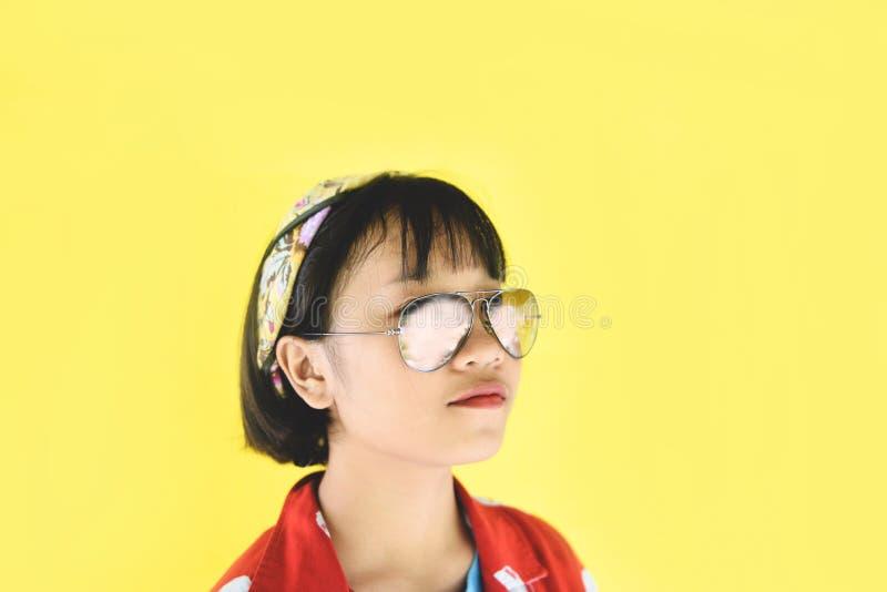 行家宜人的可爱的短发-滑稽愉快的年轻亚洲青少年的女孩时尚妇女的秀丽女孩画象有玻璃的  库存图片