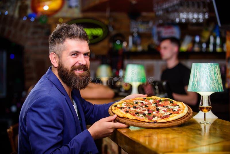 行家客户坐在酒吧柜台 人接受了可口比萨 享受您的膳食 欺诈膳食概念 饥饿的行家吃 免版税库存图片