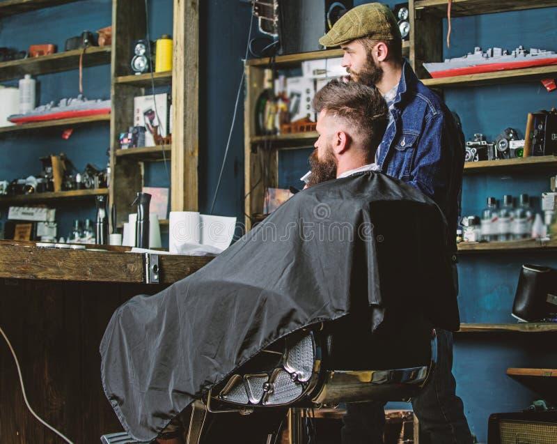 行家客户得到了新的理发 有看镜子,理发店背景的有胡子的人的理发师 理发概念 免版税库存图片