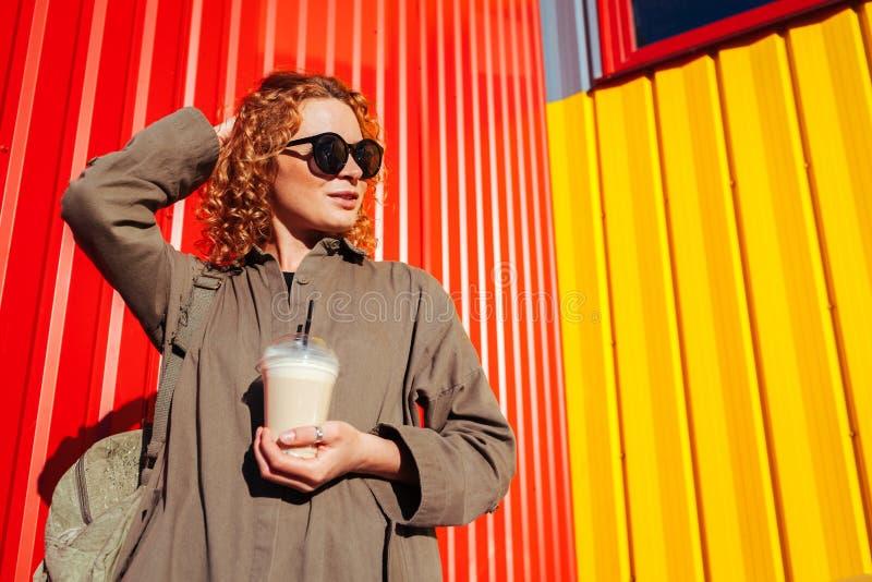 行家少妇用卷曲红色头发饮用的咖啡对红色和黄色墙壁 有背包变冷的游人 免版税库存照片
