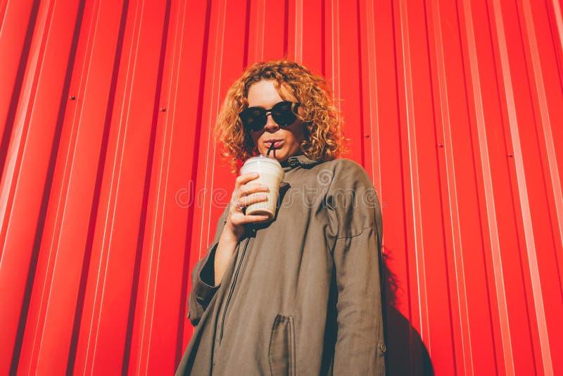行家少妇用卷曲红色头发饮用的咖啡对红色墙壁 太阳镜放松的时髦的夏天女孩 库存图片