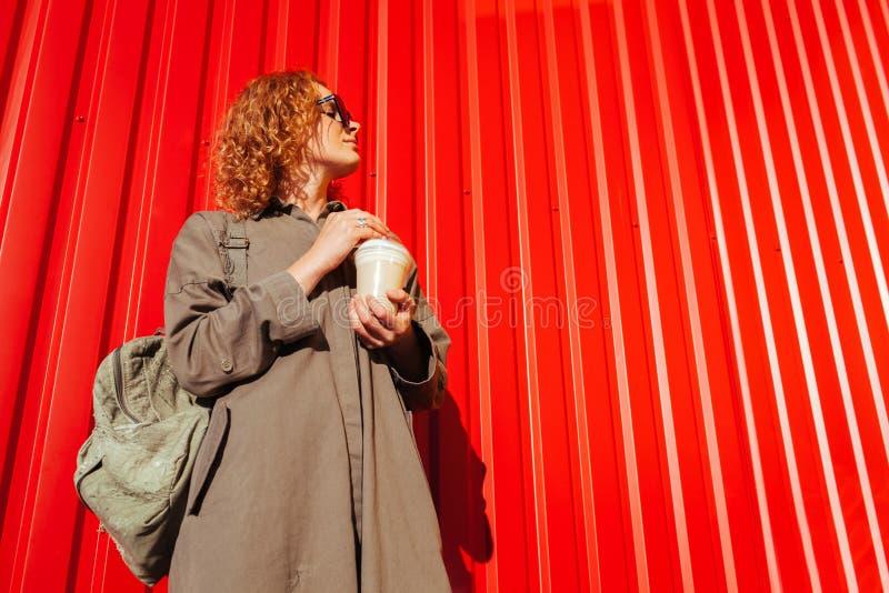 行家少妇用卷曲红色头发饮用的咖啡对红色墙壁 时髦的旅行家等待的朋友 免版税库存照片